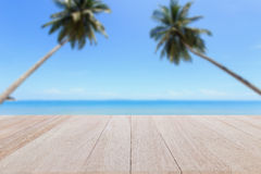 Top wooden table and blur of tropical beach background Royalty Free Stock Photos