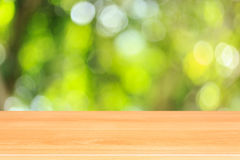 Top wooden table with sunny abstract green nature background, bl Stock Images