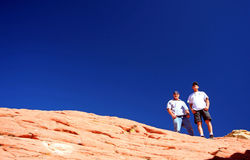 Top of the world!. Two men stand at the top of Red Rock Canyon in Las Vegas, Nevada. The rock is textured and lined and, of course, very red!  The men are on a Royalty Free Stock Photography