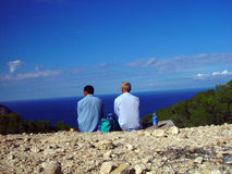 On the top of the world. Two tourists looking over the ocean in blue colors Royalty Free Stock Images