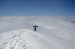 At the top of world. Climber with ice-axe is standing at a top of snow moutain. Two hands are raising. The clouds in the background accentuate the great stock photography