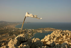 Top of the world. White flag on top of the mountain streaming in the wind. Panoramic view on a city near the sea Royalty Free Stock Images