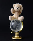 On Top of the World. Teddy bear on top of the world isolated on a black background Royalty Free Stock Image