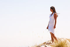 On the top of world. A young woman is standing at the top of the rock looking ahead Royalty Free Stock Image