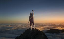 On the top of the world. Man on top of the mountain above the clouds stock photos