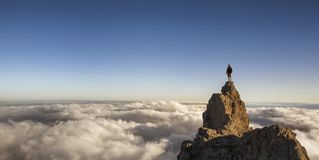 On the top of the world. Man on top of the mountain above the clouds royalty free stock photos