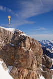 Top of the Zugspitze. Summit cross on top of the Zugspitze with clear sky and mountains in the background Stock Photography