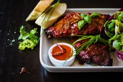Tableview of spareribs with salad, chili sauce and baguette on w Royalty Free Stock Photography