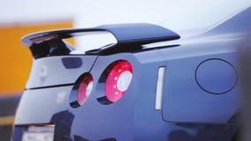 Tope del nuevo coche azul marino con las luces rojas en la calle presentación automóvil Sombras frías almacen de video