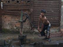 Topeless印度男孩在加尔各答,印度抽从一个街道水泵的水 库存图片