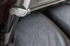 Topetón de la pierna del pasajero en asiento trasero en las líneas aéreas comerciales baratas Espacio estrecho para la rodilla de foto de archivo