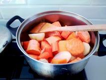 Topf mit rohem Wurzelgemüse: Karotten, Süßkartoffeln, Zwiebeln, Kartoffeln und ein hölzerner Löffel auf dem Ofen stockfoto