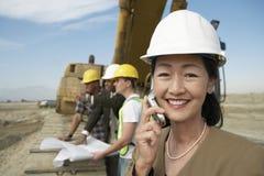 Topógrafo en el casco de protección en el teléfono móvil de Front Of Heavy Machinery Using en sitio Imagen de archivo