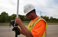 Topógrafo In Safety Gear que usa el equipo para examinar una carretera Imágenes de archivo libres de regalías