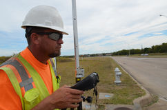 Topógrafo In Safety Gear que usa el equipo para examinar una carretera Foto de archivo libre de regalías