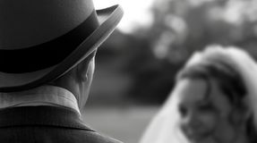 Tophat and tails. Closeup of a tophat on a grrom, with the bride in the background (blurred Stock Photo