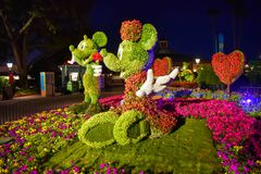 Topiaries de Mickey e de Minnie em um dia rom?ntico do piquenique no fundo da noite em Epcot em Walt Disney World 2 fotos de stock royalty free