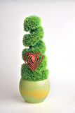 Topiary with heart ornament. Green manicured topiary in ceramic pot and red heart ornament Royalty Free Stock Photography