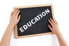 The topic of education depicted with child hands. The topic of education depicted with child hands and blackboard with text royalty free stock image