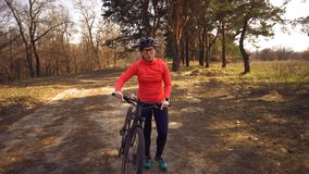 The topic health problems with athletes. Caucasian woman cyclist on mountain bike finish workout in forest. Emotion tired, hard. Fast heart beating and hard to stock photography