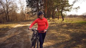 The topic health problems with athletes. Caucasian woman cyclist on mountain bike finish workout in forest. Emotion tired, hard. Fast heart beating and hard to royalty free stock photo