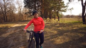 The topic health problems with athletes. Caucasian woman cyclist on mountain bike finish workout in forest. Emotion tired, hard. Fast heart beating and hard to stock image