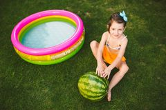 The topic proper healthy eating children. Little baby girl 4 years old caucasian sitting on green grass hugging big green round be royalty free stock photo