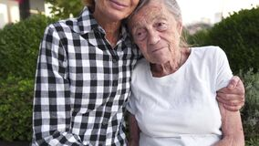Topic support and hanging out with old parents. Caucasian mature daughter expressing affection holds and strokes hands