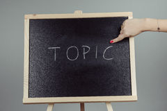 Topic written in white chalk on a black chalkboard Stock Images