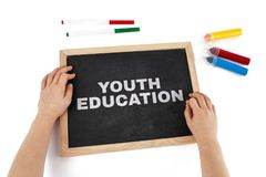 The topic of youth education depicted. The topic of youth education depicted with child hands and blackboard with text stock photography