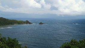 Seascape with tropical island, beach, rocks and waves. Catanduanes, Philippines. stock photos