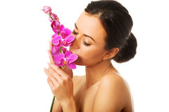 Toples kobieta z purpurową orchidei gałąź Fotografia Royalty Free