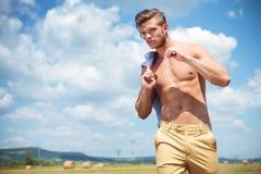 Toples mężczyzna plenerowi spacery z słomą w ręce Fotografia Stock