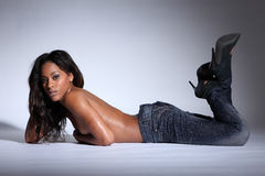 Topless african american woman lying in jeans Royalty Free Stock Images