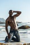 Topless afrikansk svart man på stranden Royaltyfria Bilder