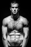 Topless de sportman bevindt zich op een zwarte achtergrond en listenin Stock Foto's