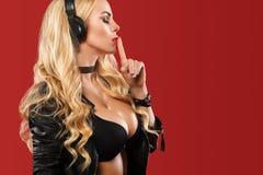 Topless discjockey och PJ, lyssnande musik för nätt blond kvinna med hennes hörlurar på den röda bakgrunden arkivbild