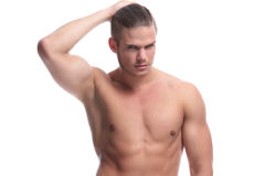 Topless fashion man holds his hair. Young fashion topless man holding back his hair while looking at the camera. isolated on white background Royalty Free Stock Images