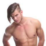 Topless fashion man looks at camera. Closeup portrait of a young fashion topless man looking at the camera while holding his hands in his back pockets. isolated Royalty Free Stock Photo