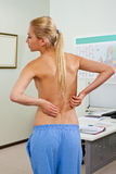 Topless female patient back pain Stock Photos