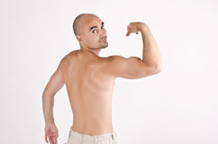 Topless fit man posing with his arm up showing his biceps. Royalty Free Stock Photos