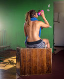 Topless girl drinking water in gym Royalty Free Stock Photo