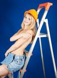 Topless girl in hardhat on stepladder. Topless girl in dungarees and hardhat on stepladder over blue Royalty Free Stock Image