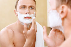 Topless man applying mean of shaving on face Stock Photos