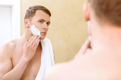 Topless man applying mean of shaving on face Stock Images