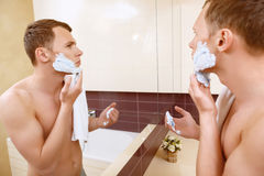 Topless man applying shaving cream on face Royalty Free Stock Image