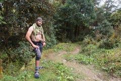 Topless man bandit wearing keffiyeh gurkha knife standing forest jungle, Nepal. Stock Image