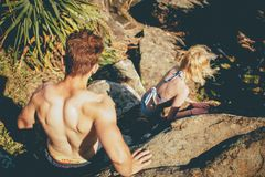 Topless Man Behind Woman Walking on Gray Rock Formation during Daytime Stock Photo