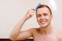 Topless man brushing his hair Royalty Free Stock Photos