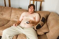 Topless man enjoying the TV Stock Photography